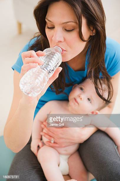 USA, New Jersey, Jersey City, Mother with baby daughter (6-11 months) drinking water