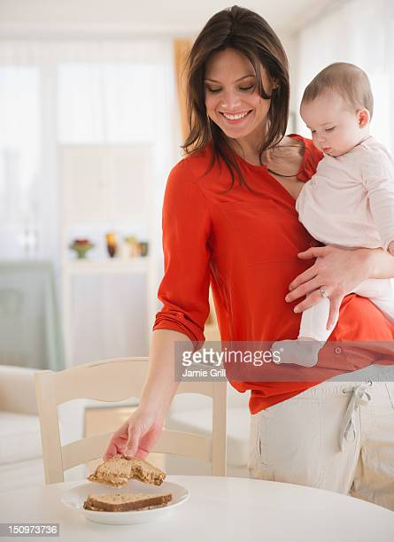usa, new jersey, jersey city, mother with baby daughter (6-11 months) eating bread - 6 11 months stock pictures, royalty-free photos & images