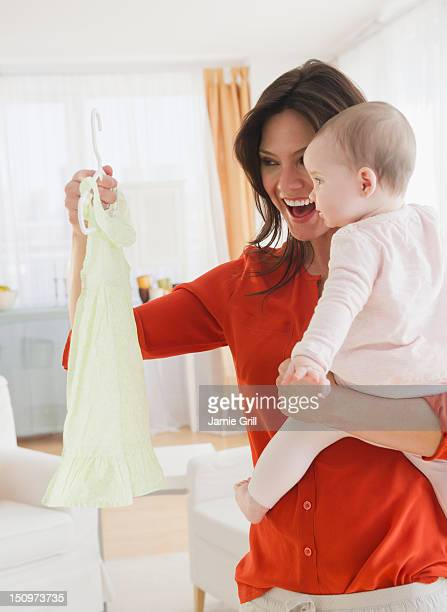 usa, new jersey, jersey city, mother with baby daughter (6-11 months) holding dress - 6 11 months stock pictures, royalty-free photos & images