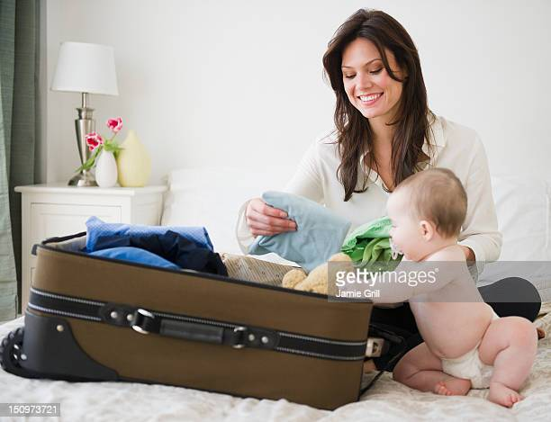 USA, New Jersey, Jersey City, Mother with baby daughter (6-11 months) packing suitcase
