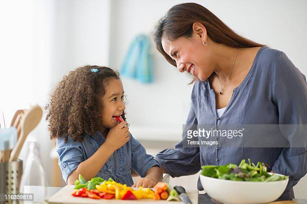 USA, New Jersey, Jersey City, mother with daughter (6-7) preparing food in kitchen