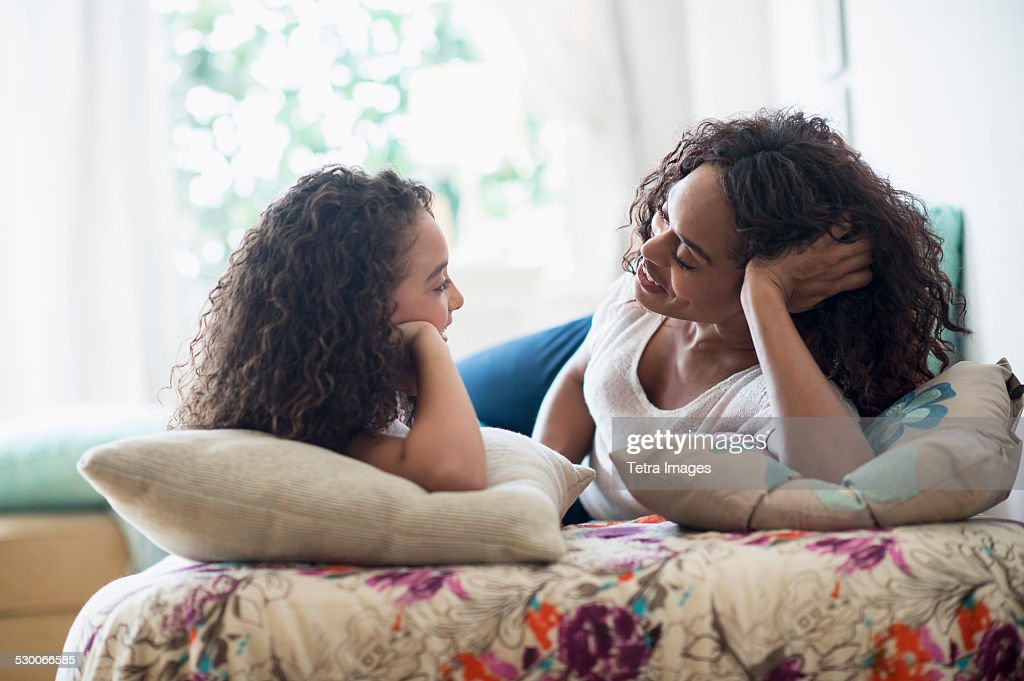 USA, New Jersey, Jersey City, Mother with daughter (8-9) talking on bed : ストックフォト