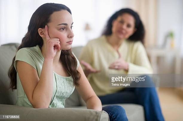 USA, New Jersey, Jersey City, Mother with teenage girl (14-15) sitting on sofa