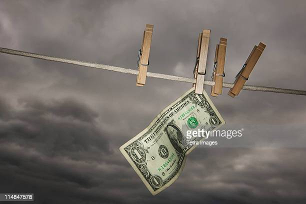 usa, new jersey, jersey city, one dollar banknote drying on clothline - money laundering stock photos and pictures
