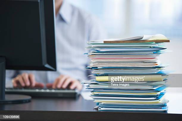 USA, New Jersey, Jersey City, Paperwork on desk by businessman using computer