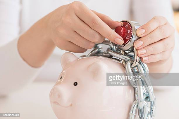 USA, New Jersey, Jersey City, Piggybank closed with chain and combination lock