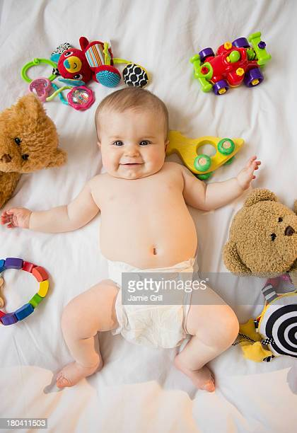 USA, New Jersey, Jersey City, Portrait of baby girl (6-11 months) lying down among toys