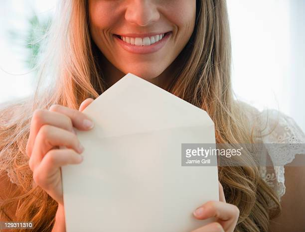 usa, new jersey, jersey city, portrait of blonde woman holding envelope - love letter stock photos and pictures