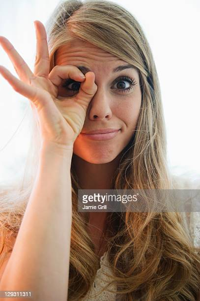 USA, New Jersey, Jersey City, Portrait of blonde woman showing ok sign