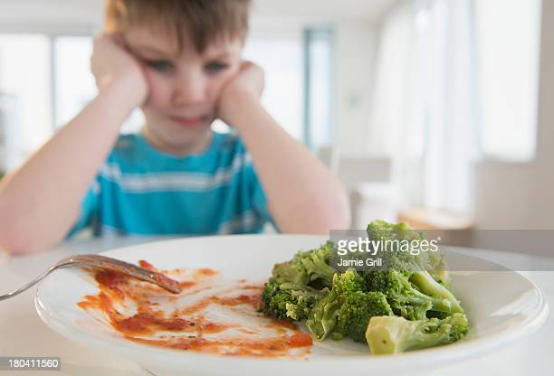 USA, New Jersey, Jersey City, Portrait of boy (4-5) annoyed to eat broccoli
