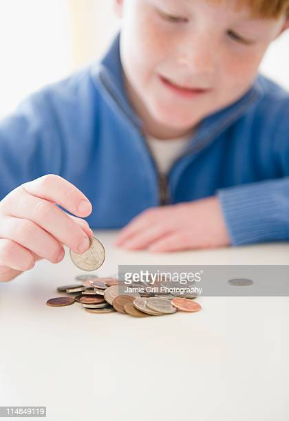 usa, new jersey, jersey city, portrait of boy (8-9) counting coins - children only stock pictures, royalty-free photos & images