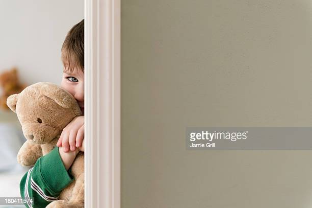 USA, New Jersey, Jersey City, Portrait of boy (4-5) hiding behind wall