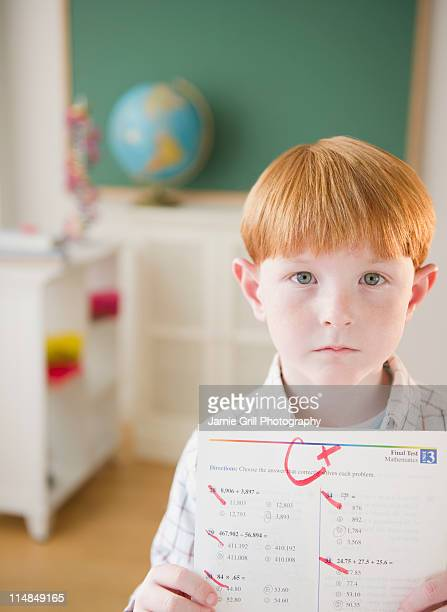 usa, new jersey, jersey city, portrait of boy (8-9) holding test results in classroom - bad bangs stock pictures, royalty-free photos & images