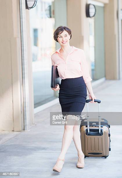 USA, New Jersey, Jersey City, Portrait of business woman pulling suitcase
