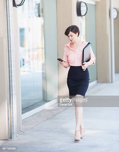 USA, New Jersey, Jersey City, Portrait of business woman walking and text messaging