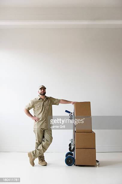 USA, New Jersey, Jersey City, Portrait of delivery man standing next to push cart