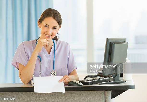 USA, New Jersey, Jersey City, Portrait of female nurse at nurse's station in hospital