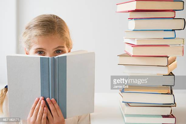 USA, New Jersey, Jersey City, Portrait of girl (8-9) reading book
