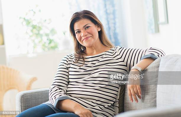 usa, new jersey, jersey city, portrait of happy woman sitting on sofa - mid adult women stock pictures, royalty-free photos & images
