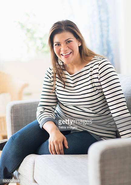 USA, New Jersey, Jersey City, Portrait of happy woman sitting on sofa