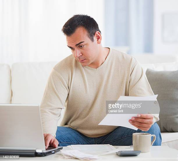 USA, New Jersey, Jersey City, Portrait of man doing paperwork in living room