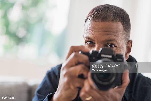 USA, New Jersey, Jersey City, Portrait of man holding digital camera