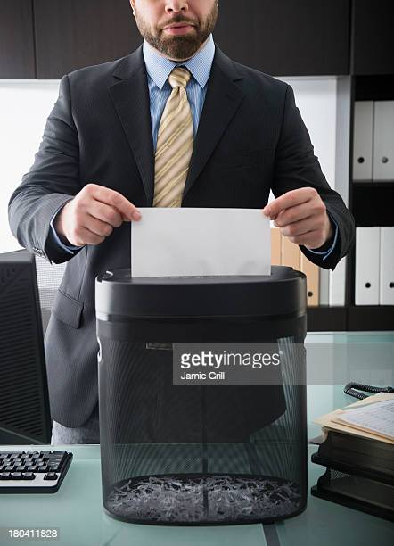 USA, New Jersey, Jersey City, Portrait of man putting paper into paper shredder