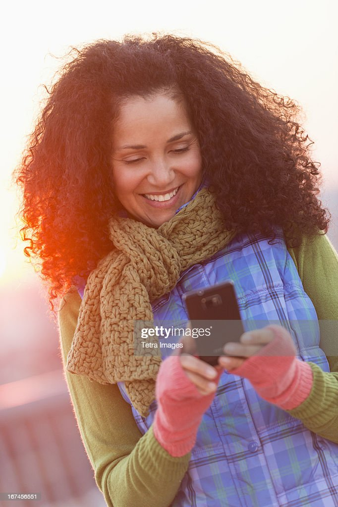 USA, New Jersey, Jersey City, Portrait of mid adult woman using mobile phone at sunset : Stock Photo