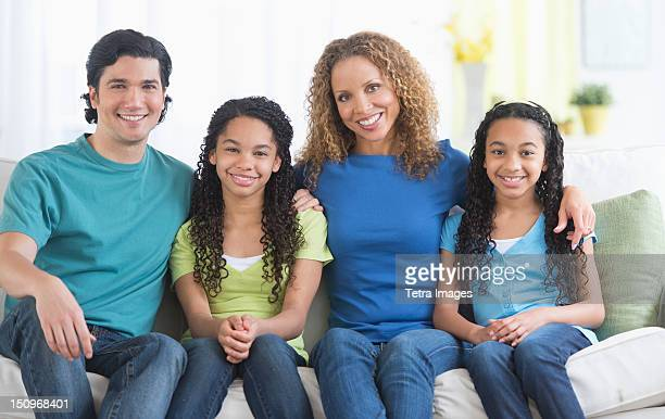 USA, New Jersey, Jersey City, Portrait of parents with daughters (10-13) sitting on sofa