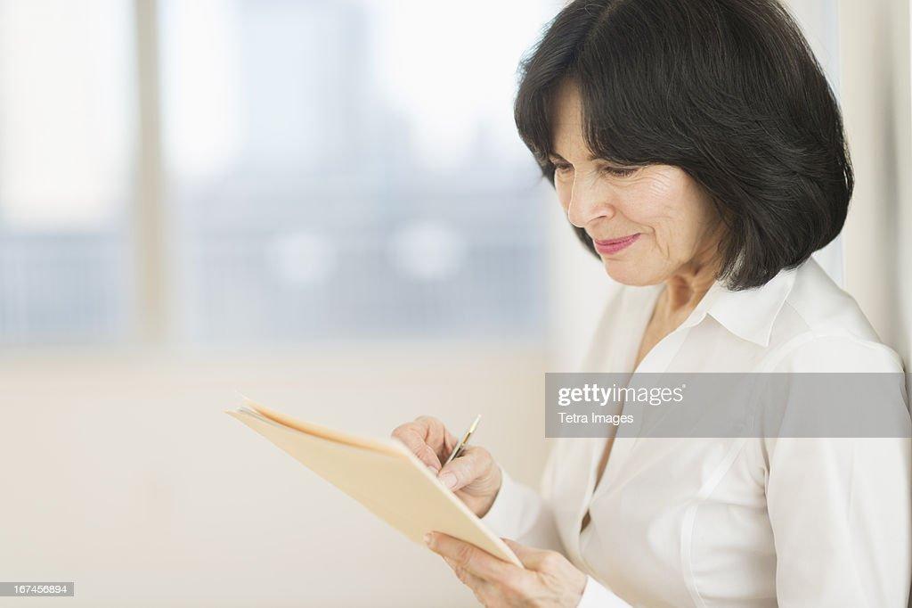 USA, New Jersey, Jersey City, Portrait of senior businesswoman writing : Stock Photo