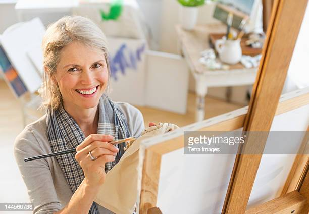 USA, New Jersey, Jersey City, Portrait of senior woman painting on canvas