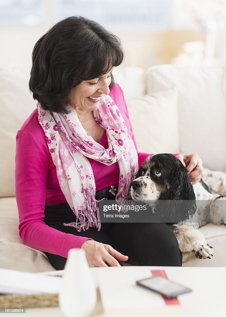 USA, New Jersey, Jersey City, Portrait of senior woman sitting on sofa with her dog : Stock Photo