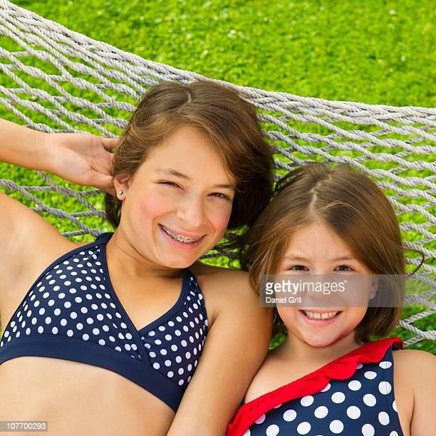 usa, new jersey, jersey city, portrait of sisters (8-9, 12-13) lying in hammock - solo bambine femmine costume da bagno foto e immagini stock