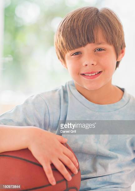 USA, New Jersey, Jersey City, Portrait of smiling boy (10-11 years) with basketball ball