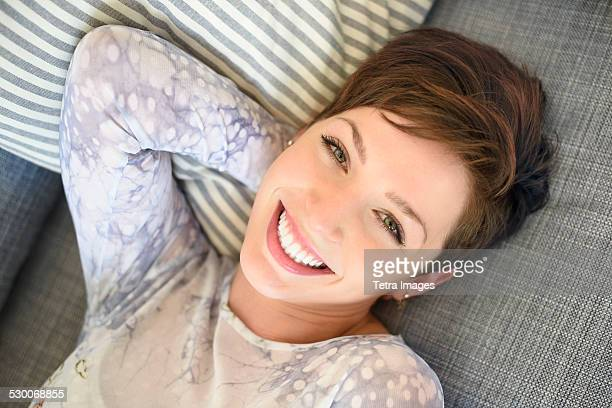 USA, New Jersey, Jersey City, Portrait of smiling woman lying on sofa