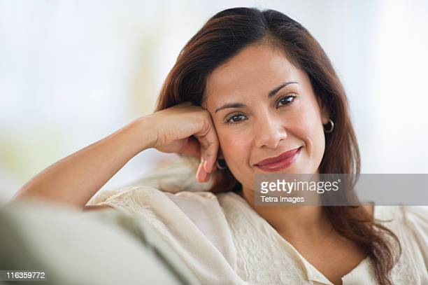 USA, New Jersey, Jersey City, portrait of smiling woman sitting on sofa