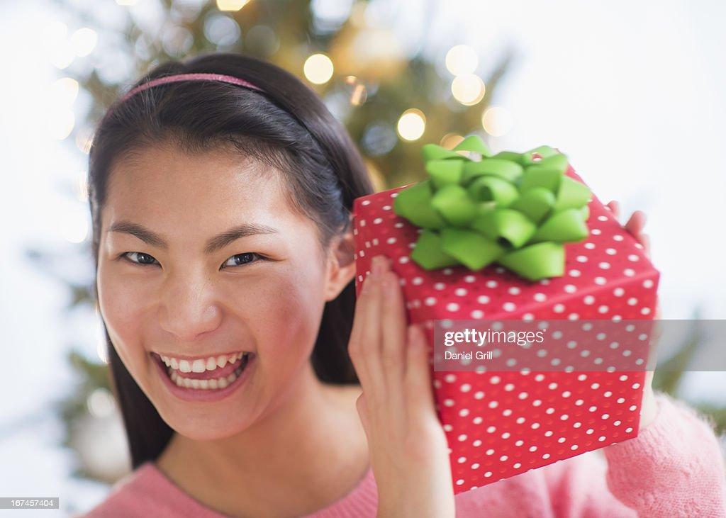 USA, New Jersey, Jersey City, Portrait of teenage girl ( 16-17 years) holding Christmas gift : Stock Photo