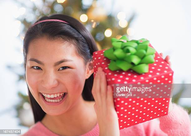 usa, new jersey, jersey city, portrait of teenage girl ( 16-17 years) holding christmas gift - 16 17 years stock pictures, royalty-free photos & images