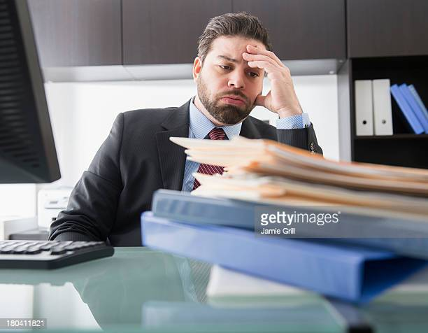 USA, New Jersey, Jersey City, Portrait of tired businessman sitting in office