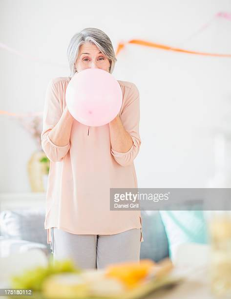 USA, New Jersey, Jersey City, Portrait of woman blowing balloon
