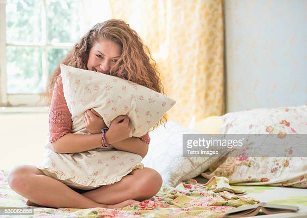 USA, New Jersey, Jersey City, Portrait of woman embracing pillow