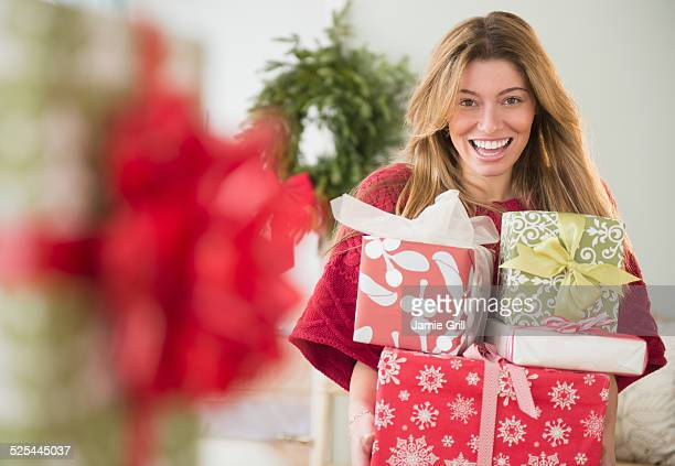 USA, New Jersey, Jersey City, Portrait of woman holding christmas presents