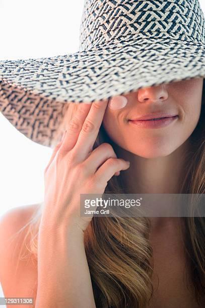 USA, New Jersey, Jersey City, Portrait of woman in straw hat applying moisturizer