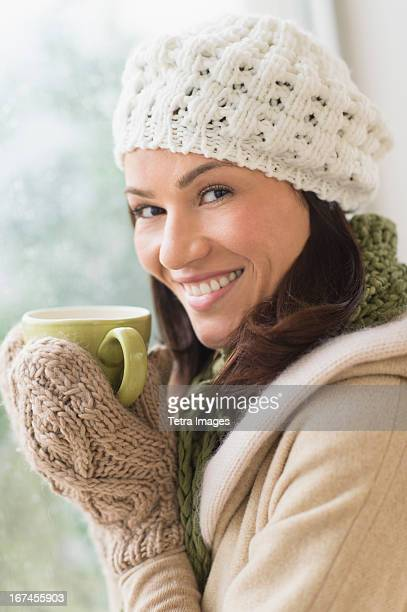 usa, new jersey, jersey city, portrait of woman in warm clothes holding mug - one mid adult woman only stock pictures, royalty-free photos & images