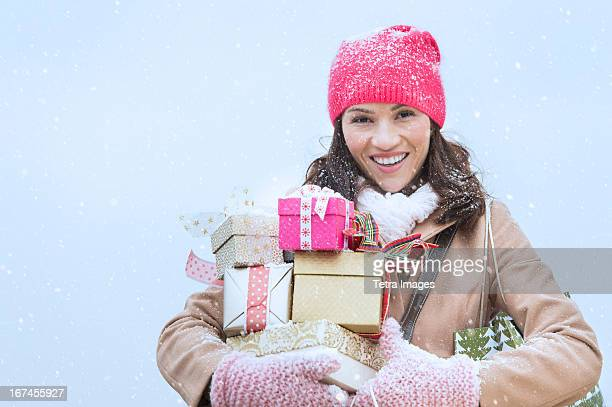 USA, New Jersey, Jersey City, Portrait of woman in winter clothes carrying presents