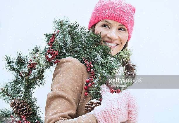 usa, new jersey, jersey city, portrait of woman in winter clothes carrying wreath - mitten stock pictures, royalty-free photos & images