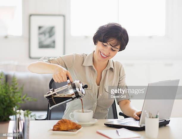USA, New Jersey, Jersey City, Portrait of woman pouring coffee in front of laptop