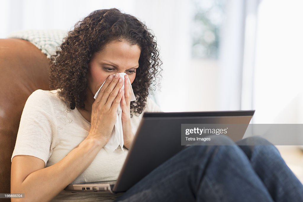 USA, New Jersey, Jersey City, Portrait of woman sitting with laptop and blowing nose : Stock Photo