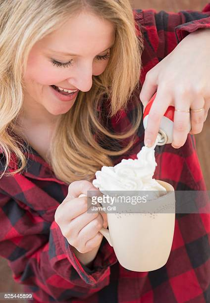 USA, New Jersey, Jersey City, Portrait of woman spraying whipped cream into hot chocolate