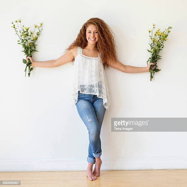 USA, New Jersey, Jersey City, Portrait of woman with bunches of flowers in hands